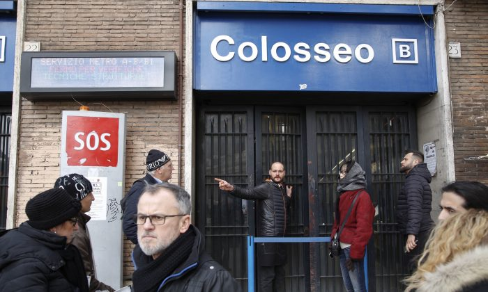 A man gives indications to tourists after the Colosseo subway station was closed following three earthquakes which hit central Italy in the space of an hour, shaking the same region that suffered a series of deadly quakes last year, in Rome on Jan. 18, 2017. (AP Photo/Domenico Stinellis)