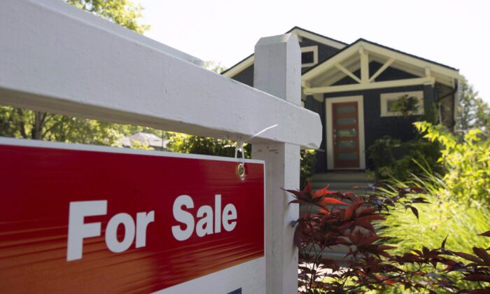 A sold sign is pictured outside a home in Vancouver on June 28, 2016. Canada's national housing is raising the cost of home insurance to strengthen lenders' capital bases. (The Canadian Press/Jonathan Hayward)