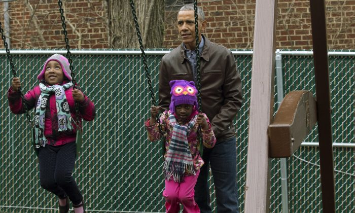 U.S. President Barack Obama pushes children on swings on 'Malia and Sasha's Castle', a play-set that was formerly used by the Obama children at the White House and donated by the Obama family, during a service event for Martin Luther King Jr. Day at the Jobs Have Priority Naylor Road Family Shelter in Washington, DC on Jan. 16, 2017. (MICHAEL REYNOLDS-Pool/Getty Images)
