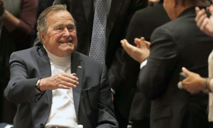 """Former President George H.W. Bush acknowledges the crowd at his presidential library before his son former President George W. Bush discusses his new book """"41: A Portrait of My Father"""" in College Station, Texas, in this file photo. (Bob Daemmrich/Texas Tribune via AP, Pool, File)"""