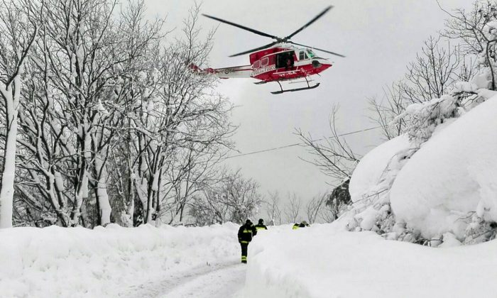 An Italian firefighters helicopter flies during rescue operations in the area where an hotel was hit by an avalanche in Farindola, Italy, on Jan. 19, 2017. (Matteo Guidelli/ANSA via AP)