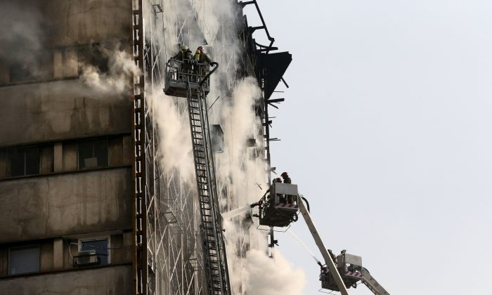 Iranian firefighters work to extinguish fire of the Plasco building in central Tehran, Iran on Jan. 19, 2017. (AP Photo/Vahid Salemi)