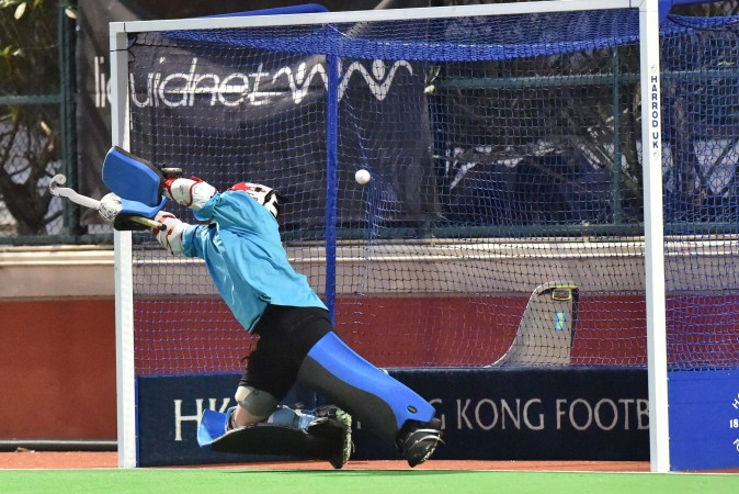 HKFC goalie gets a touch on this penalty  stroke by SSSC but the ball flies into the net  to pull a goal back to make the score 2-1.(Bill Cox/Epoch Times)