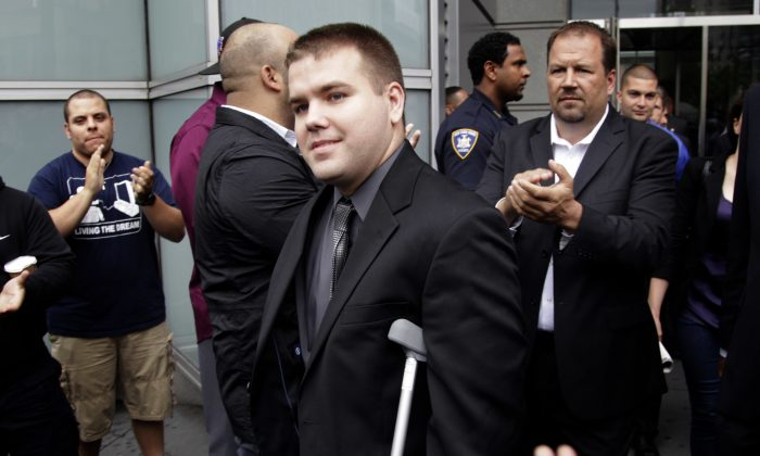 In this file photo, police officers and supporters clap as Officer Richard Haste, center, exits the courthouse after posting bail in New York, on June 13, 2012. (AP Photo/Seth Wenig, File)