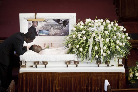 In this file photo, Franclot Graham leans over his son, Ramarley Graham, in his casket before funeral services in the Bronx borough of New York, on Feb. 18, 2012. (AP Photo/John Minchillo)