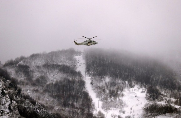 A Finance Police helicopter hovers above the town of Farindola, central Italy, Thursday, Jan. 19, 2017. Days of heavy snowfall had knocked out electricity and phone lines in many central Italian towns and hamlets, compounded by four powerful earthquakes that struck the region on Wednesday, and an avalanche which buried a four-star spa hotel near Farindola. (AP Photo/Gregorio Borgia)