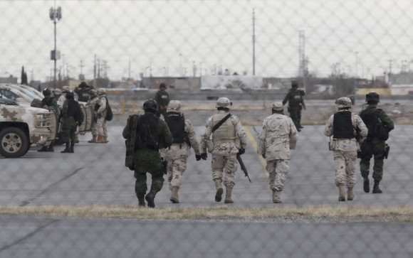 """Soldiers walk at the airport after the extradition of drug lord Joaquin """"El Chapo"""" Guzman in Ciudad Juarez, Mexico, Thursday, Jan. 19, 2017. Mexico's Foreign Relations Department announced Guzman was handed over to U.S. authorities for transportation to the U.S. on Thursday, the last day of President Barack Obama's administration and a day before Donald Trump is to be inaugurated. (AP Photo/Christian Torres)"""