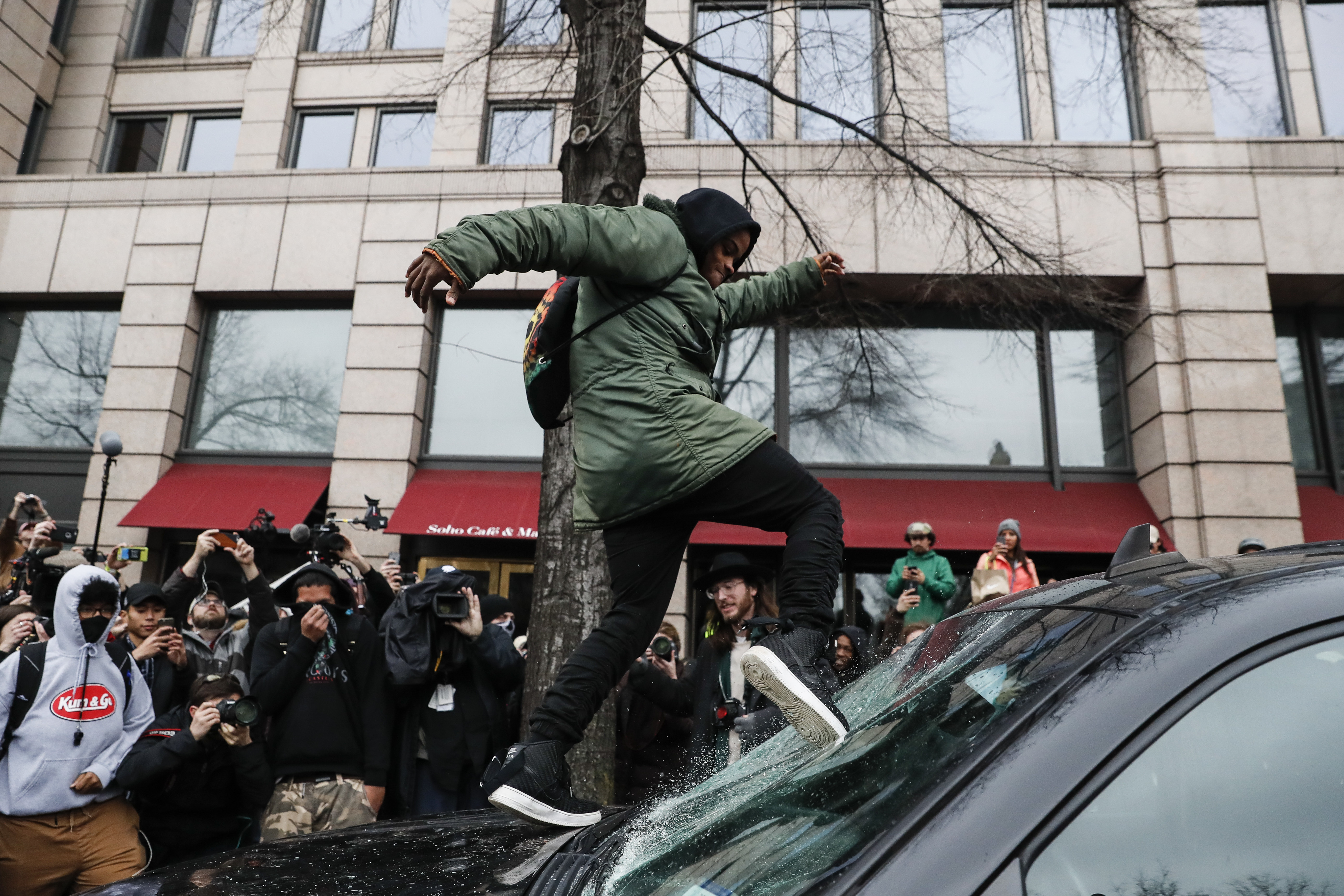 A protestor kicks in a windshield during a demonstration in Washington on Jan. 20, 2017, after the inauguration of President Donald Trump. (AP Photo/John Minchillo)