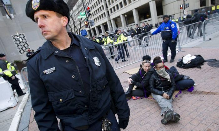 Demonstrators sit near a security checkpoint as police officers let people pass to the inauguration, Friday, Jan. 20, 2017 in Washington, ahead of President-elect Donald Trump's inauguration. ( AP Photo/Jose Luis Magana)