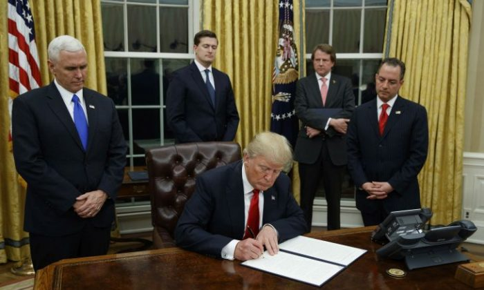 President Donald Trump, flanked by Vice President Mike Pence and Chief of Staff Reince Priebus, signs his first executive order on health care, in the Oval Office of the White House in Washington on Jan, 20, 2017. (AP Photo/Evan Vucci)