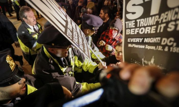 Police push protesters off the sidewalk in front of the National Press Building ahead of the presidential inauguration, Thursday, Jan. 19, 2017, in Washington. (AP Photo/John Minchillo)