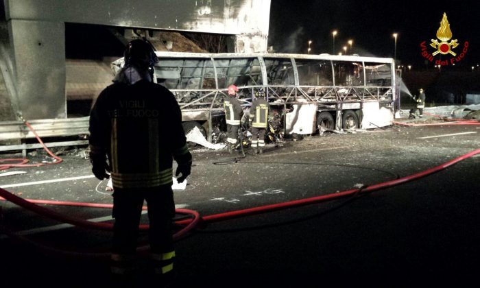 Firefighters inspect the burned hulk of a bus that crashed and burst into flames near Verona, northern Italy, Saturday, on Jan. 21, 2017. (Italian Firefighters/ANSA via AP)