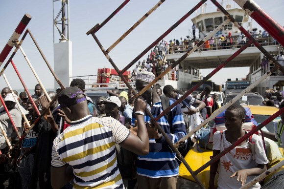 A ferry bringing back people who fled arrives at the port in Banjul, Gambia, as it reopens Saturday Jan. 21, 2017. life slowly returns to the Gambian capital as Gambia's defeated leader Yahya Jammeh announced early Saturday he has decided to relinquish power, after hours of last-ditch talks with regional leaders and the threat by a regional military force to make him leave. (AP Photo/Jerome Delay)