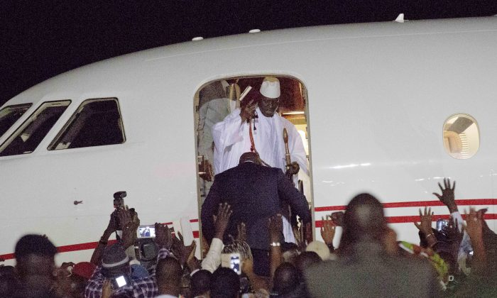Gambia's defeated leader Yahya Jammeh waves to supporters as he departs at Banjul airport on Jan. 21, 2017. Jammeh announced early Saturday he has decided to relinquish power, after hours of last-ditch talks with regional leaders and the threat by a regional military force to make him leave. (AP Photo/Jerome Delay)