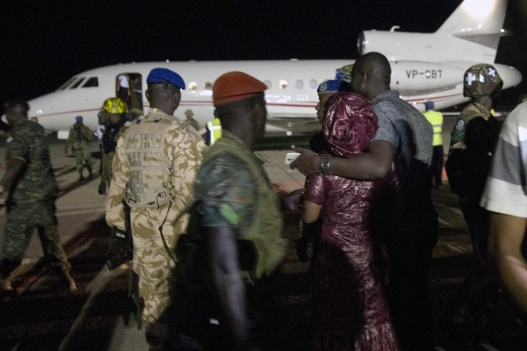 Supporters of Gambia's defeated leader Yahya Jammeh watch as his plane prepares for takeoff as he departs at Banjul airport on Jan. 21, 2017. Jammeh announced early Saturday he has decided to relinquish power, after hours of last-ditch talks with regional leaders and the threat by a regional military force to make him leave. (AP Photo/Jerome Delay)