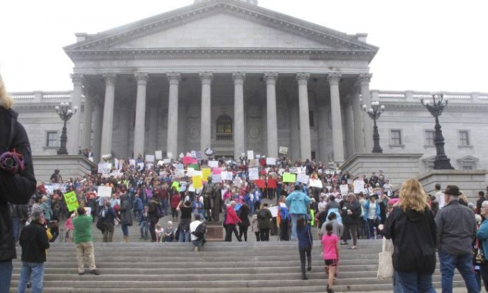 Thousands of women gather for the Stand Up Rally for women and minority rights on Saturday, Jan. 21, 2017, at the Statehouse in Columbia, S.C. Similar rallies were being held across the country to protest President Donald Trump and his administration. (AP Photo/Jeffrey Collins)