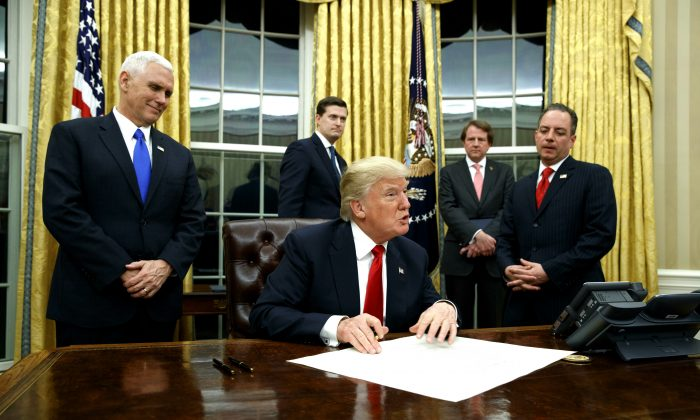 Vice President Mike Pence watches at left as President Donald Trump prepares to sign his first executive orderi n the Oval Office of the White House in Washington on Jan. 20, 2017. (AP Photo/Evan Vucci)