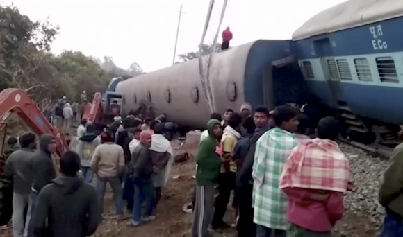 Rescuers and onlookers stand around coaches of a derailed passenger train in Kuneru, Andhra Pradesh, southern India, on Jan. 22, 2017. (KK Production via AP)