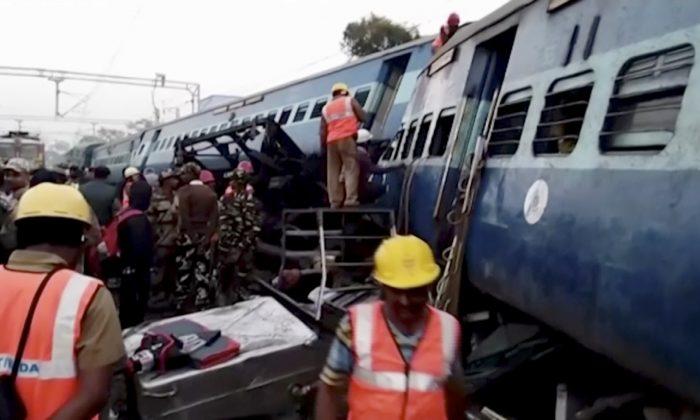 Rescuers work around coaches of a derailed passenger train in Kuneru, Andhra Pradesh, southern India, on Jan. 22, 2017. (KK Production via AP)