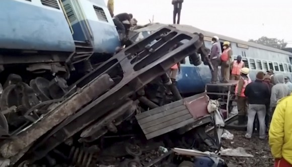 Rescuers stand around coaches of a derailed passenger train in Kuneru, Andhra Pradesh, southern India, on Jan. 22, 2017. (KK Production via AP)
