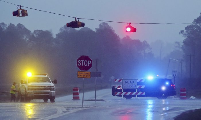 A Brooks County Sheriff and officials block Highway 122 as power line workers repair a downed pole in the background near Barney, Ga., on Jan. 22, 2017. (AP Photo/Phil Sears)