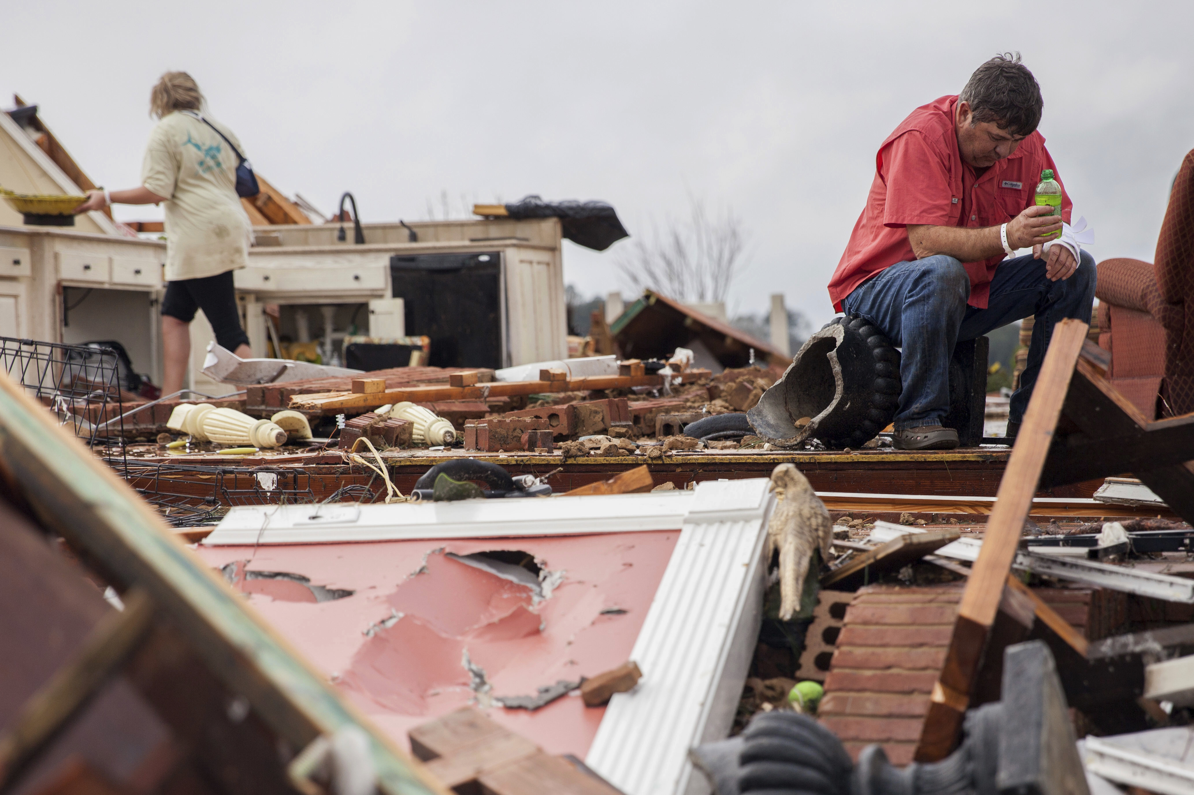 Jeff Bullard sits in what used to be the foyer of his home as his daughter, Jenny Bullard, looks through debris at their home that was damaged by a tornado in Ga., on Jan. 22, 2017, in Adel. (AP Photo/Branden Camp)