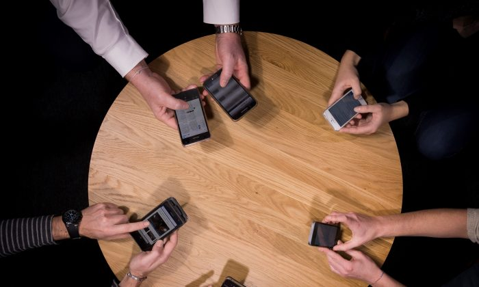 People hold their smartphones around a conference table in France on Jan. 5, 2016. Effectively partnering public relations with digital advertising could generate positive results for small businesses. (Lionel Bonaventure/AFP/Getty Images)