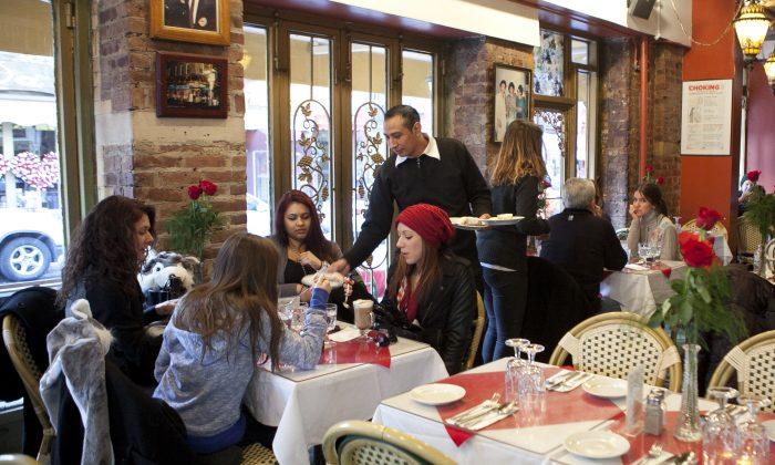 A waiter attends to customers at a restaurant in Manhattan, New York, on Feb. 17, 2014. (Samira Bouaou/Epoch Times)