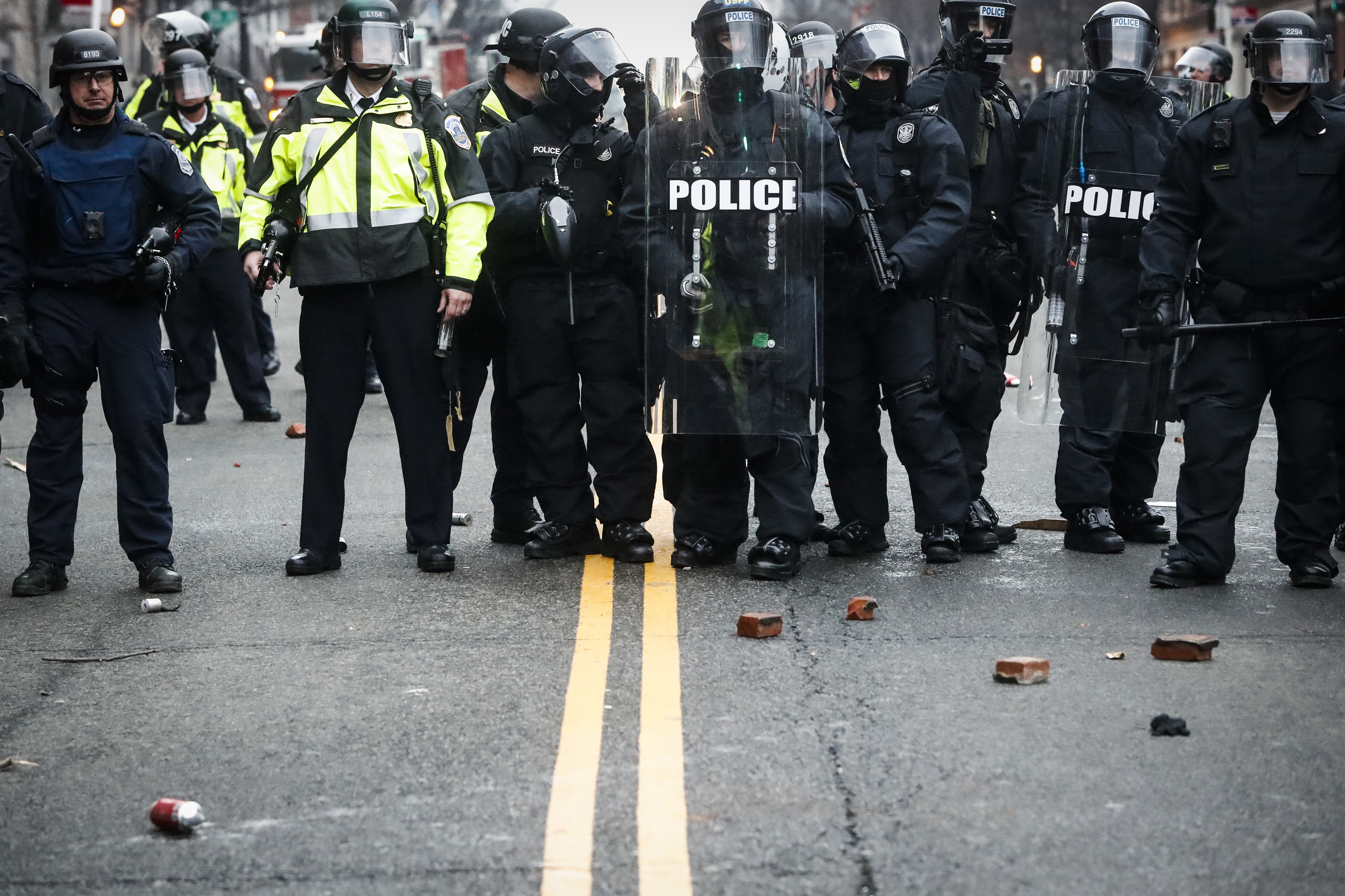 Bricks thrown by protestors rest at the feet of police officers during a demonstration after the inauguration of President Donald Trump in Washington on Jan. 20, 2017. (AP Photo/John Minchillo)