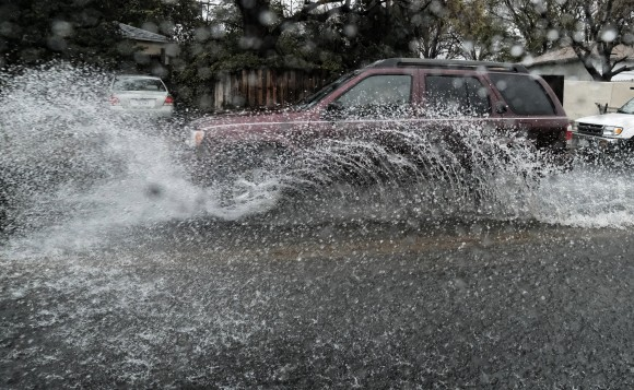 A car drives through a flooded street in Los Angeles on Sunday, Jan. 22, 2017. California residents evacuated neighborhoods below hillsides scarred by wildfires as the third, and largest, in the latest series of storms brought powerful rain Sunday and warnings about flash flooding and mudslides. (AP Photo/Richard Vogel)
