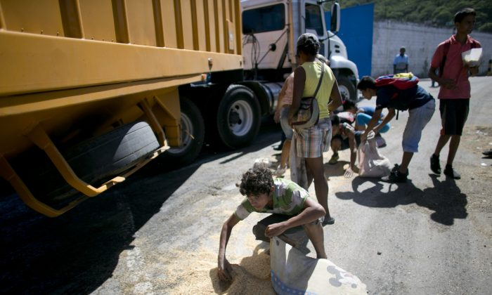 FILE - In this Nov. 14, 2016 file photo, a youth uses his pillow as a bag to collect rice from the pavement that shook loose from a food cargo truck waiting to enter the port in Puerto Cabello, Venezuela, the port that handles the majority of Venezuela's food imports. The calls by members of Congress on both sides of the aisle to sanction Venezuelan officials for profiting from food shortages come in response to an Associated Press investigation that found trafficking in hard-to-find food has become big business in Venezuela, with the military at the heart of the graft. (AP Photo/Ariana Cubillos, File)