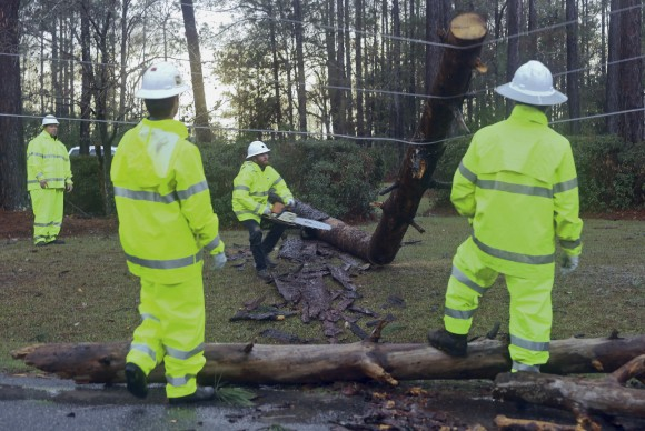 """At center, David Barnes, with Colquitt EMC, lunges backwards as a limb he has just cut snaps into the air from tension on downed power lines Sunday Jan. 22, 2017 in Valdosta, Ga. The National Weather Service said Sunday that southern Georgia, northern Florida and the corner of southeastern Alabama could face """"intense and long track"""" tornadoes, scattered damaging winds and large hail. (AP Photo/Phil Sears)"""