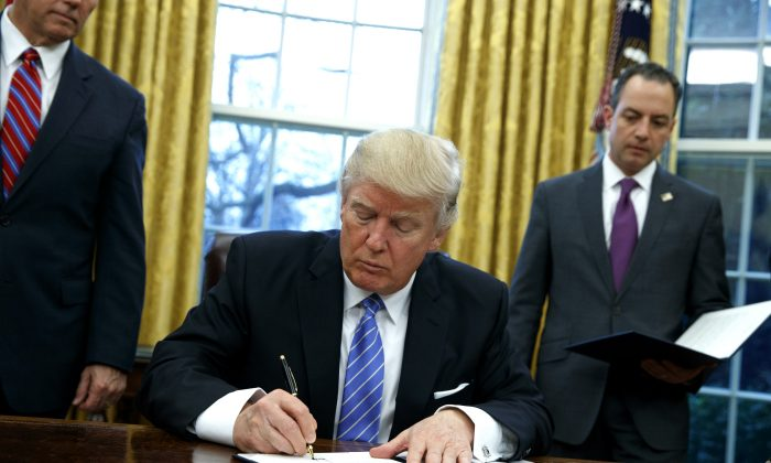 President Donald Trump signs an executive order to withdraw the U.S. from the 12-nation Trans-Pacific Partnership trade pact agreed to under the Obama administration on Jan. 23, 2017, in the Oval Office of the White House in Washington. (AP Photo/Evan Vucci)