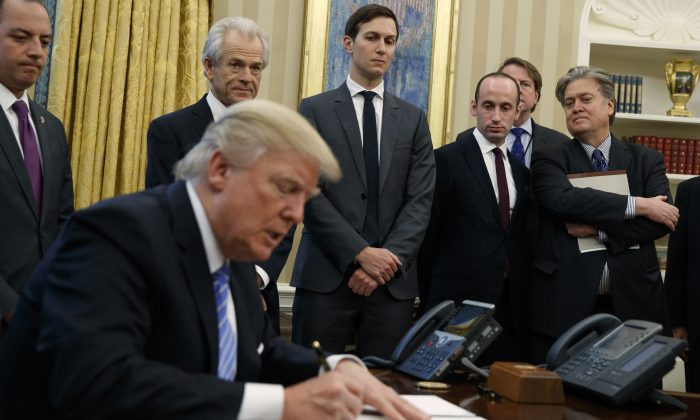 (L-R) White House Chief of Staff Reince Priebus, National Trade Council adviser Peter Navarro, Senior Adviser Jared Kushner, policy adviser Stephen Miller, and chief strategist Steve Bannon watch as President Donald Trump signs an executive order in the Oval Office of the White House in Washington on Jan. 23, 2017. (AP Photo/Evan Vucci)