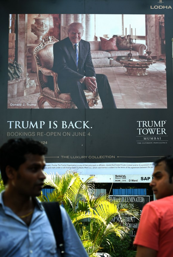 Indian men walk by a billboard for the upcoming luxury residential apartment complex Trump Tower Mumbai, which bears the name of billionaire real estate tycoon and US President Donald Trump, in Mumbai on June 3, 2016. (INDRANIL MUKHERJEE/AFP/Getty Images)