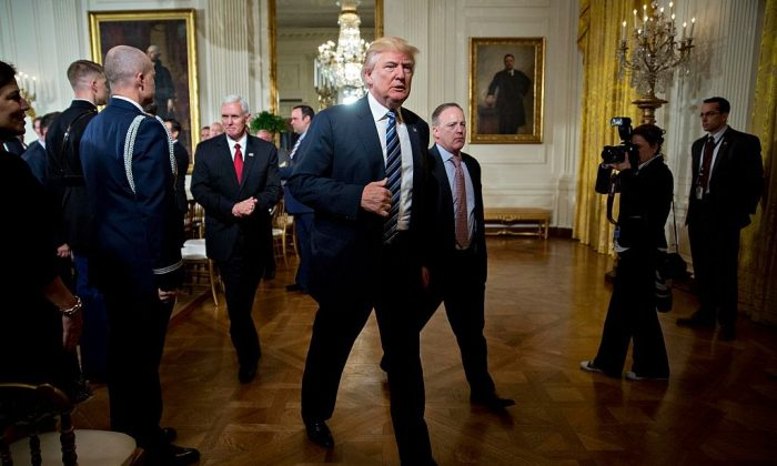 President Donald Trump walks out with U.S. Vice President Mike Pence and Sean Spicer, White House press secretary (R) during a swearing in ceremony of White House senior staff in the East Room of the White House in Washington on Jan. 22, 2017. (Andrew Harrer-Pool/Getty Images)
