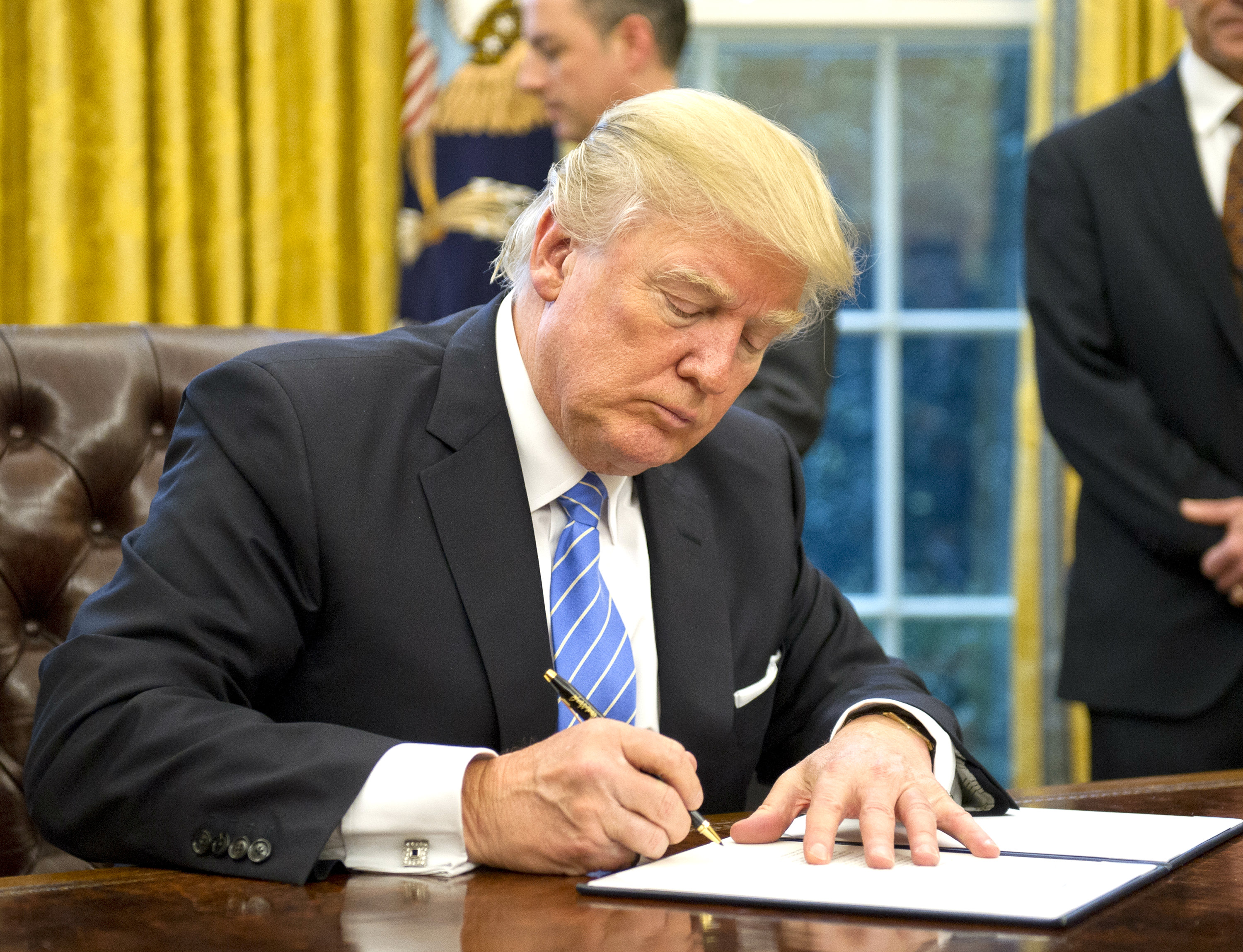 President Donald Trump signs the last of three Executive Orders in the Oval Office of the White House in Washington, DC, on Jan. 23, 2017. (Ron Sachs - Pool/Getty Images)