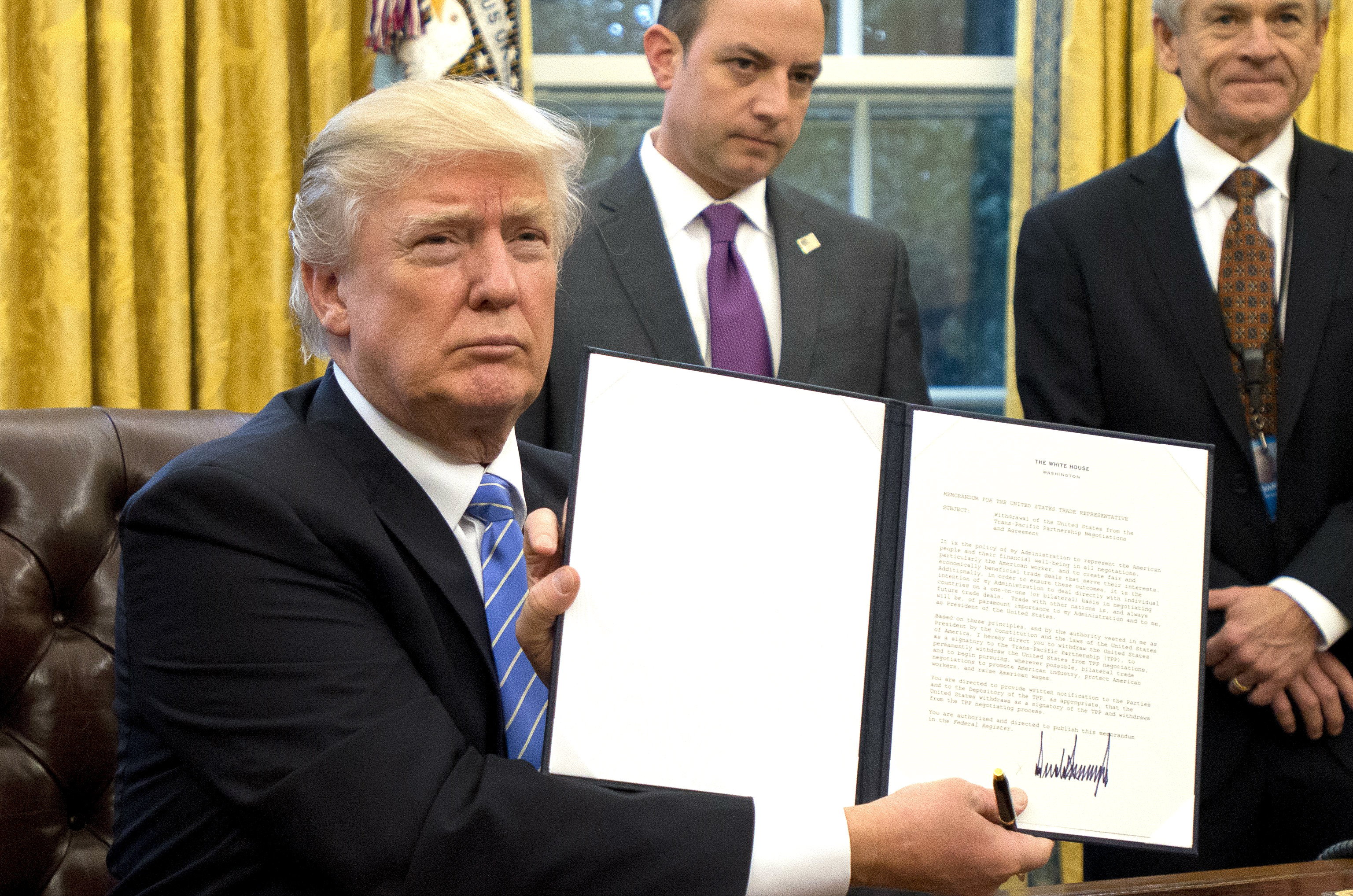 President Donald Trump shows the Executive Order withdrawing the US from the Trans-Pacific Partnership after signing it in the Oval Office of the White House in Washington, DC on Jan. 23, 2017. (Ron Sachs - Pool/Getty Images)