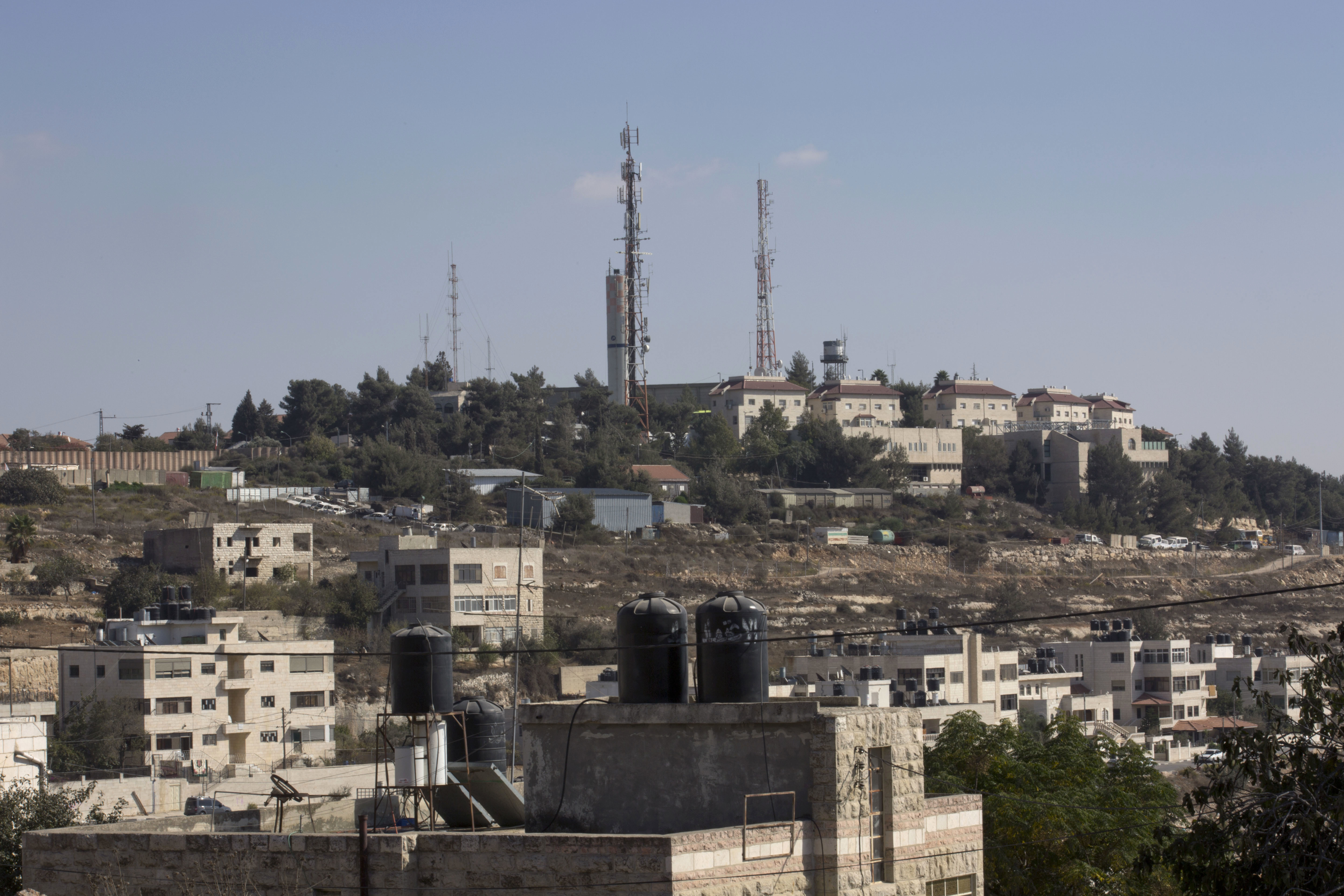 Part of the Israeli settlement of Psagot, background, overlooking Palestinian houses, in a suburb of the West Bank city of Ramallah on Oct. 24, 2016. (AP Photo/Nasser Nasser)