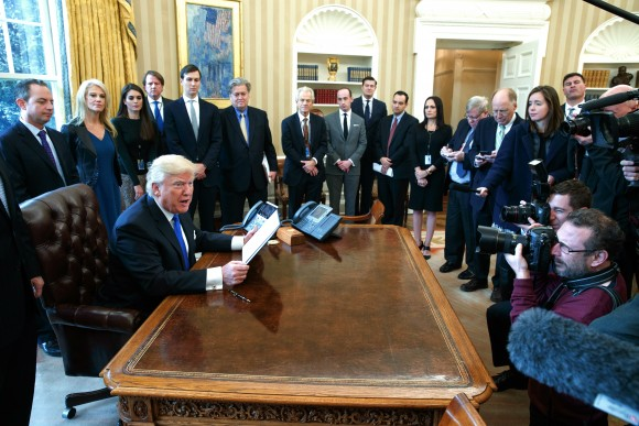 President Donald Trump talks with reporters in the Oval Office of the White House in Washington on Jan. 24, 2017, before signing an executive order on the Dakota Access pipeline. (AP Photo/Evan Vucci)