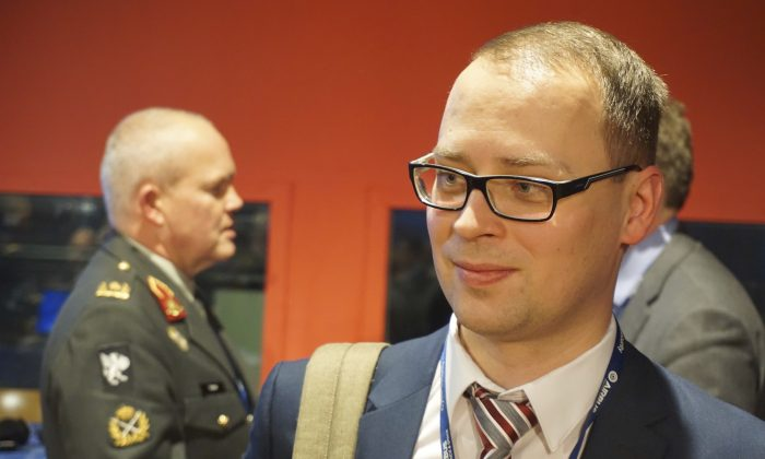 Estonian defense official Erki Kodar chats with a conference goer as part of a Cyber Security conference held in Lille, northern France on Jan. 24, 2017. Estonia is experimenting with the idea of cyberconscription, giving draftees with tech skills the chance to step into roles defending the military's electronic infrastructure. (AP Photo/Raphael Satter)
