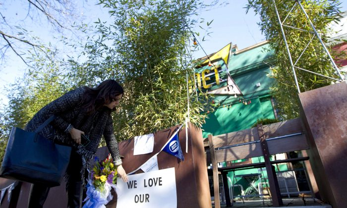 A woman places a support banner with flowers outside Comet Ping Pong in Washington on Dec. 5, 2016. A fake news story prompted a man to fire an assault rifle inside the popular pizza shop the previous day. (AP Photo/Jose Luis Magana)