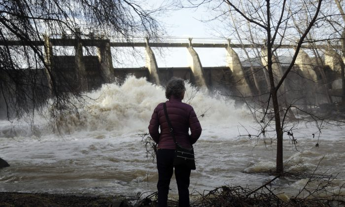Chris Buchanan watches the overflow at a dam on Vasona Lake after a series of storms Tuesday, Jan. 24, 2017, in Los Gatos , Calif. (AP Photo/Marcio Jose Sanchez)