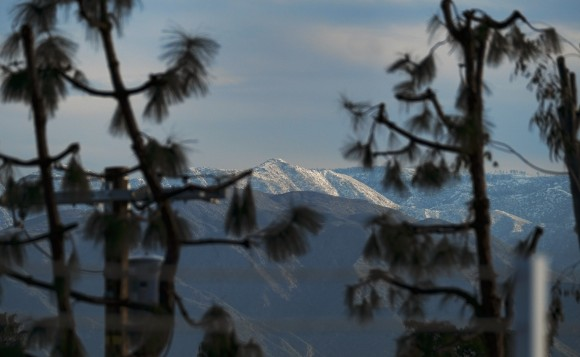Mountain tops East of Los Angeles are covered with snow seen from Los Angeles, Tuesday, Jan. 24, 2017. After years of drought and barren slopes, skiers and boarders have a bonanza of snow at resorts from the Sierra Nevada to the mountain ranges of Southern California following a barrage of storms. East of Los Angeles, the Bear Mountain-Snow Summit resorts report their largest January total, 70 inches, while Mountain High says the latest storm dropped the most snow in five years. (AP Photo/Richard Vogel)