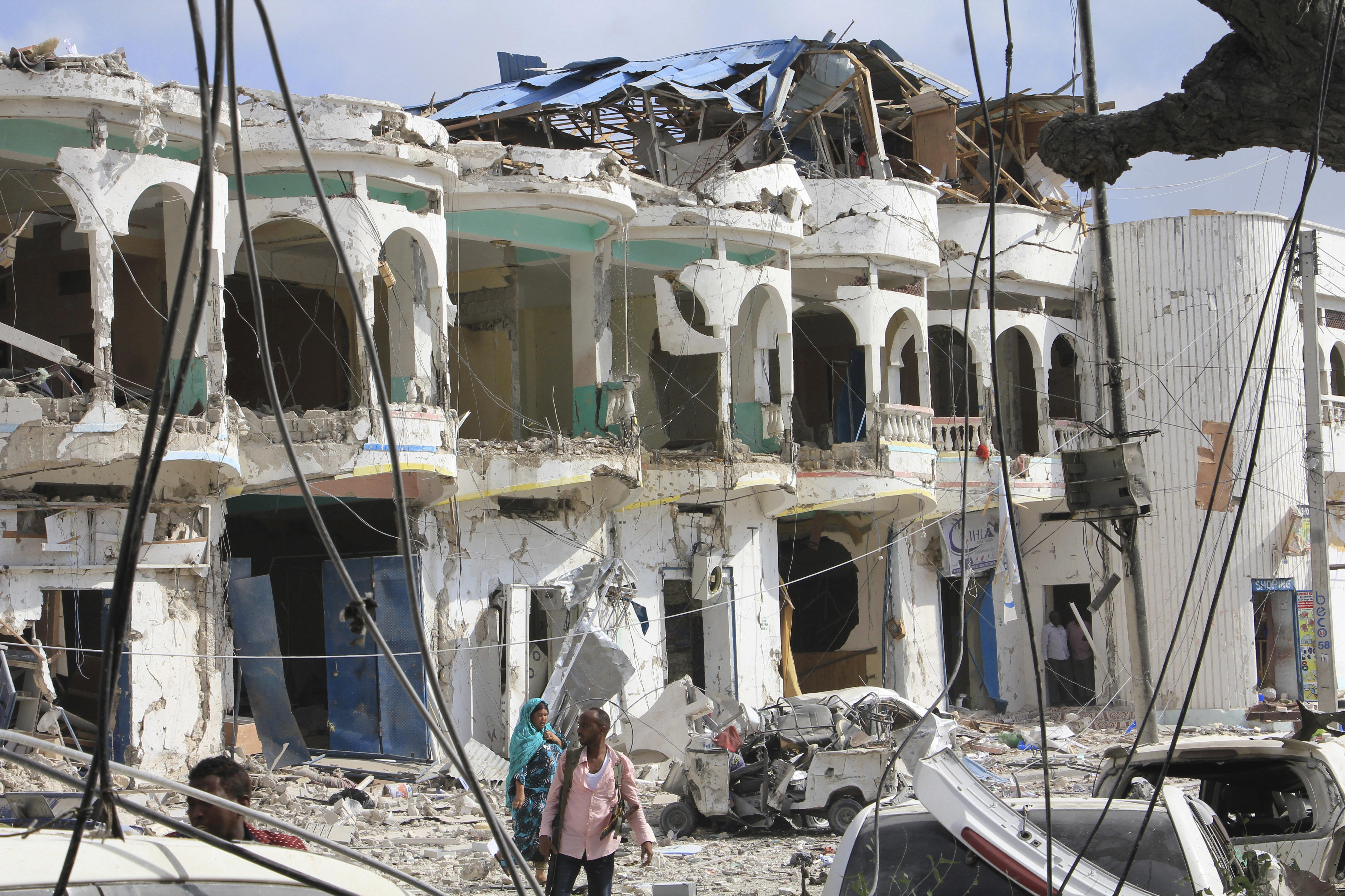 Somalis walk near a hotel heavily damaged by a car bomb blast in Mogadishu, Somalia on Jan 25, 2017. (AP Photo/Farah Abdi Warsameh)
