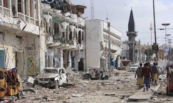 Somalis walk near the destroyed hotel and cars in Mogadishu, Somalia on Jan 25, 2017. (AP Photo/Farah Abdi Warsameh)