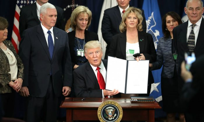 U.S. President Donald Trump (C) displays one of the four executive orders he signed during a visit to the Department of Homeland Security in Washington, DC, on Jan. 25, 2017. Trump signed four executive orders related to domestic security and to begin the process of building a wall along the U.S.-Mexico border. (Chip Somodevilla/Getty Images)