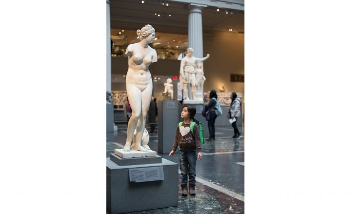A girl looks at a Roman statue of a wounded Amazon at the Metropolitan Museum of Art in New York on Dec. 29, 2016. (Samira Bouaou/Epoch Times)