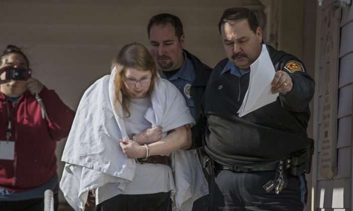 """FILE - In this Jan. 8, 2017 file photo, Sara Packer, center, handcuffed, the adoptive mother of Grace Packer, is led out of District Court in Newtown, Pa.,  by Pennsylvania Constables and taken into custody. Packer, whose teenage daughter's dismembered remains were found in the woods last fall, has been charged along with her boyfriend Jacob Sullivan with killing the girl in a """"rape-murder fantasy"""" the couple shared, a prosecutor said. (Michael Bryant/The Philadelphia Inquirer via AP, File)"""