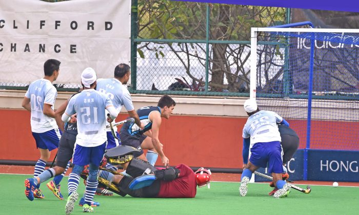 HKFC-A player Angus Allen (obscured) behind KNS-A's No 29 Harmanpreet Singh converts this goal from a partial block of an Istiaq Ahmed shot by the KNS goalie to regain the lead at 2-1 in their HKHA Premier Group A league at HKFC on Sunday Jan 22. The final score was 3-1 to HKFC. (Bill Cox/Epoch Times).